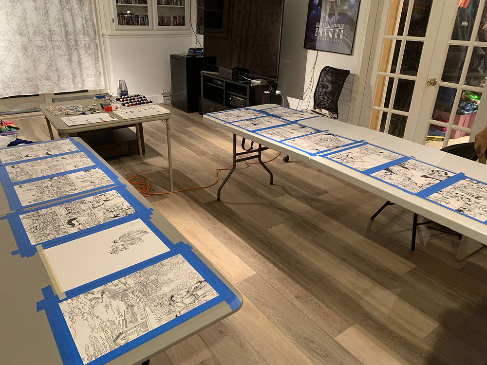inked comic pages taped to tables in preparation for painting