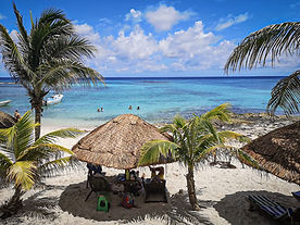 A palapa at the beach with the Mexican Caribbean in the background