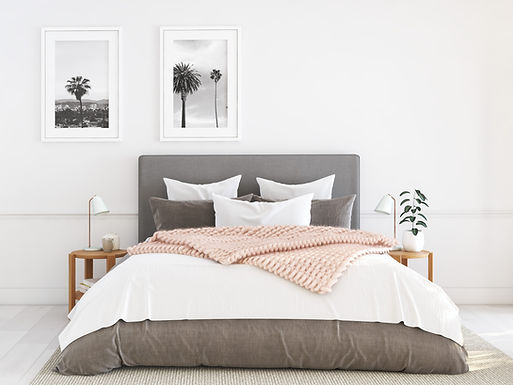Grey upholstered Bed frame grey comforter, grey and white pillows, blush large knit blanket, round night stands, white and gold goose neck side lamps, framed wall art of palm trees, white walls, white wood floors