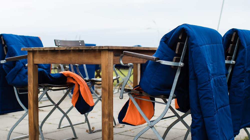 Sittingsuits resting on restaurant chairs