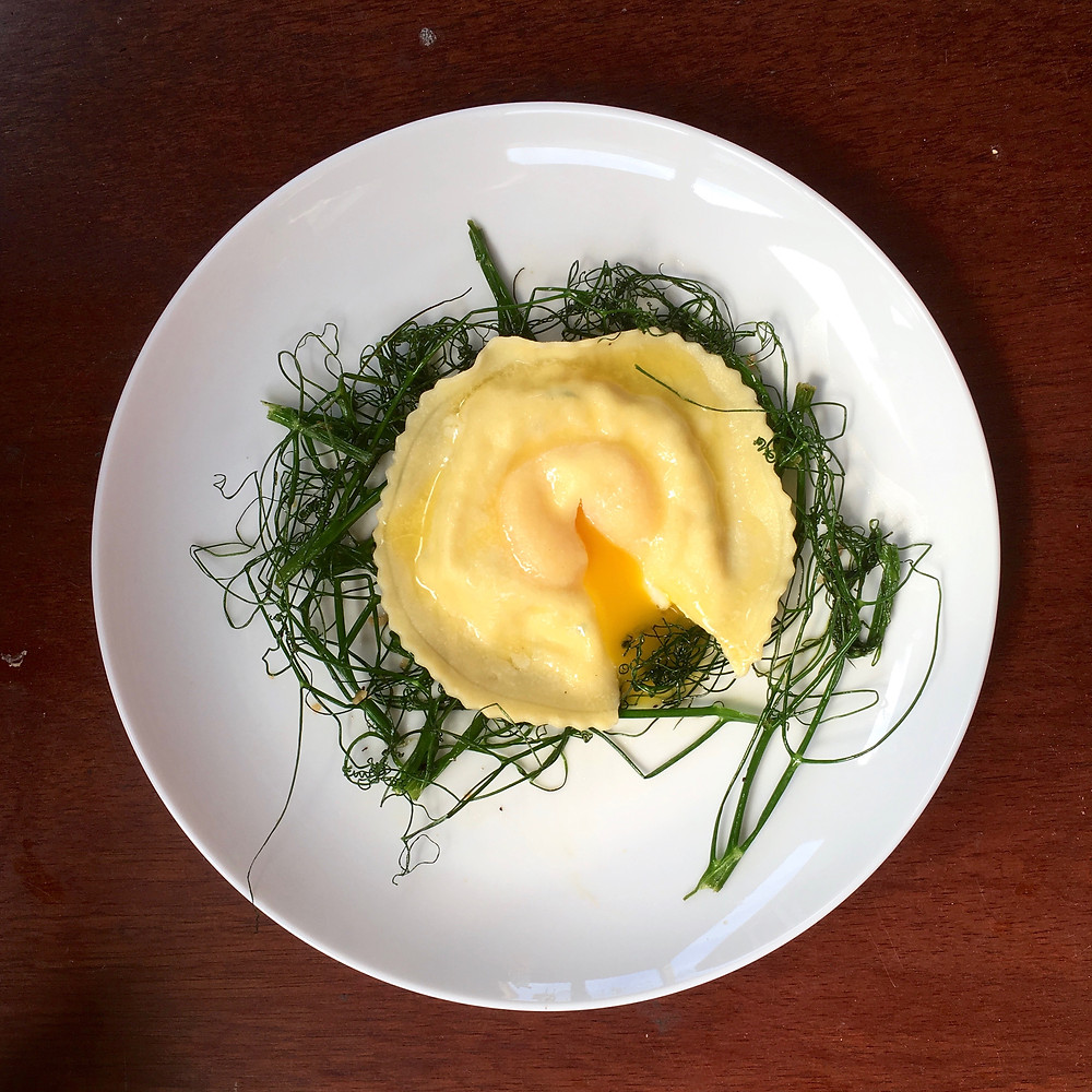 Raviolo with egg yolk and pea shoots