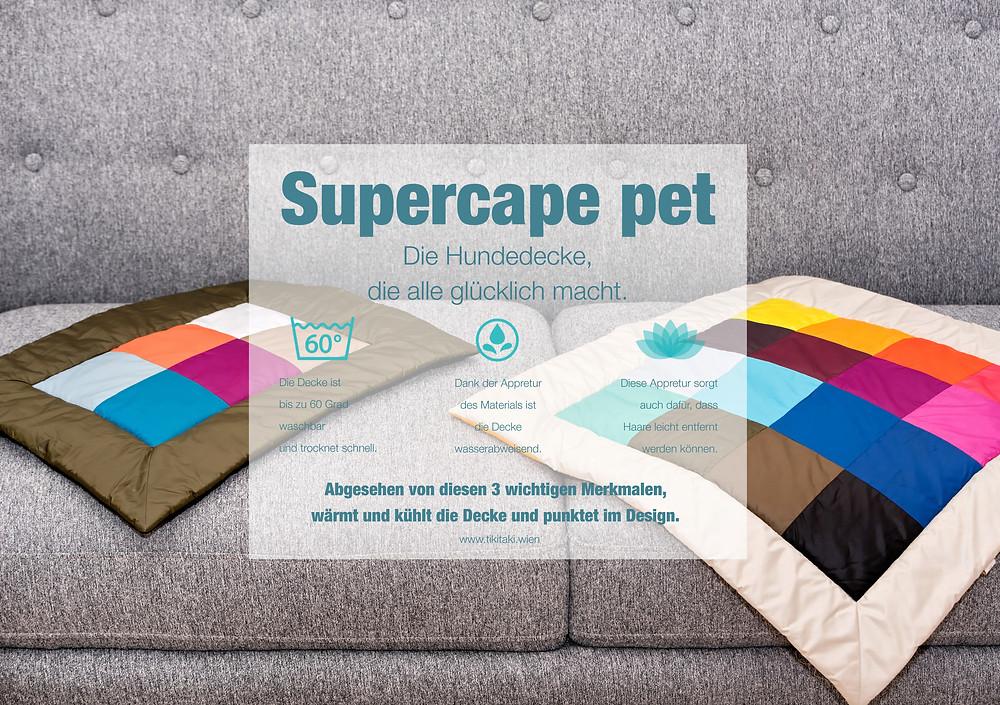 Zwei Hundedecken auf einem grauen Sofa. Links Supercape Pet Mini und rechts Supercape Pet Rainbow.