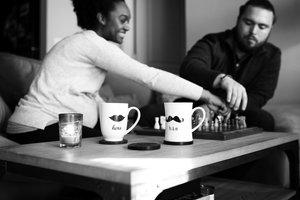 A pregnant couple engaging in their favorite past time (a game of chess and tea from their wedding mugs) during an in home maternity session