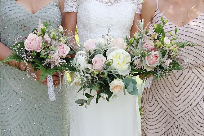 brud med brudtärnor och brudbukett i rosa , vitt och grönt