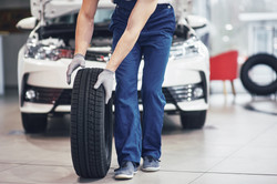 Mechanic holding a tire tire at the repa