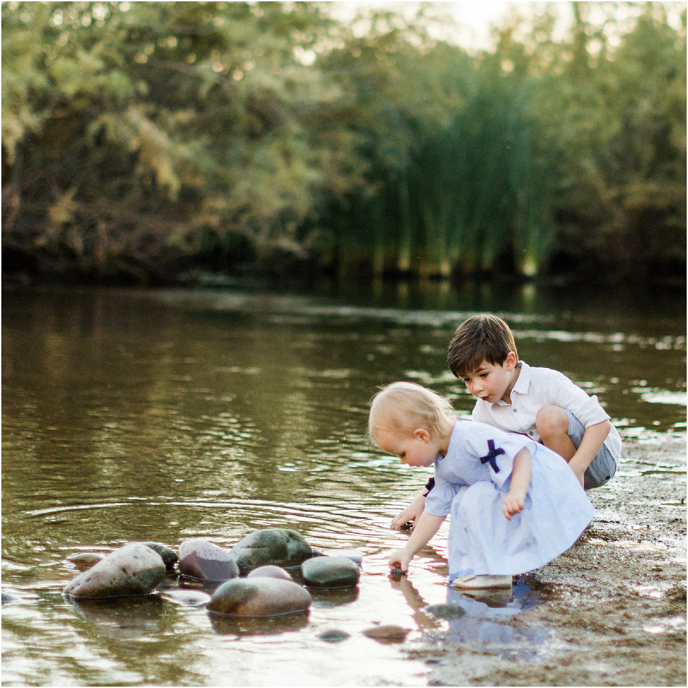 sweet candid photo of two children playing by a lake