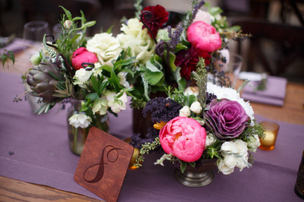 Autumn inspired organic flower arrangements with plum, pink, white and green. Wood carved table numbers and amber votives complete the look.