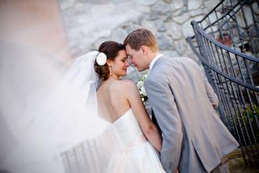 Veil in the wind shot of bride & groom