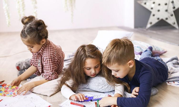 three-focused-children-are-playing-floor