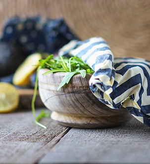 A beeswax food wrap covering arugula in wooden bowl . Close up shot. Waste free. Eco friendly_edited