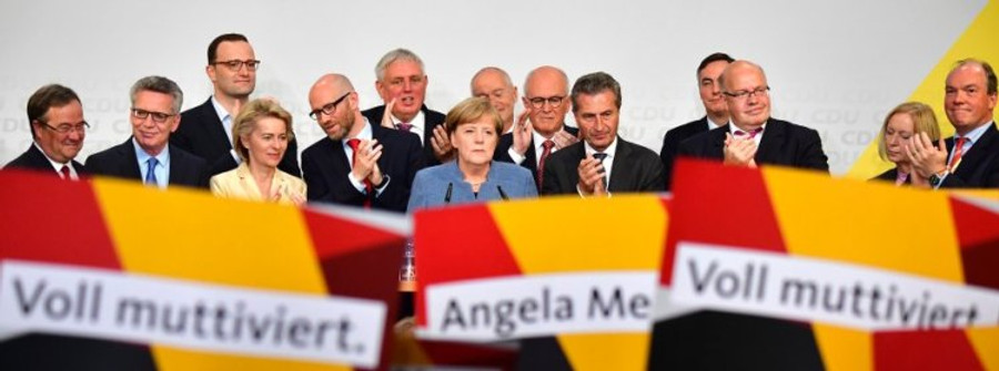 German Chancellor and Christian Democrats party (CDU) leader Angela Merkel (C) speaks on stage surrounded by her team during the election night event at the CDU party's headquarters in Berlin during the general election on September 24, 2017. Germany voted in a general election expected to hand Chancellor Angela Merkel a fourth term, while the hard-right Alternative for Germany (AfD) party is predicted to win its first seats in the national parliament. / AFP PHOTO / Tobias SCHWARZ