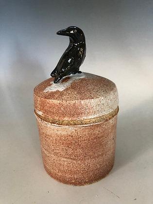 Crow sitting on a jar