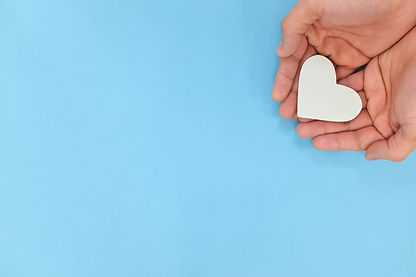 Hands holding a white heart in blue back