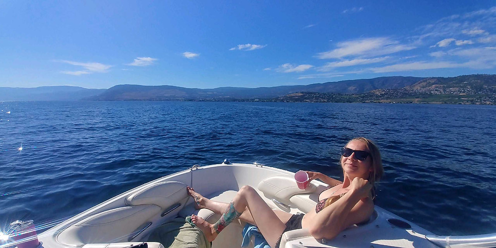 Blonde girl on a lake with blue skies
