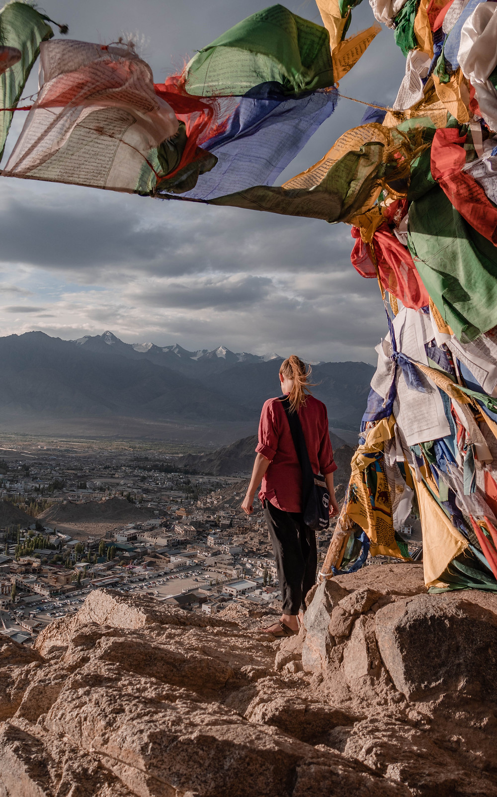 Girl overlooking Indian town with Buddhist prayer flags