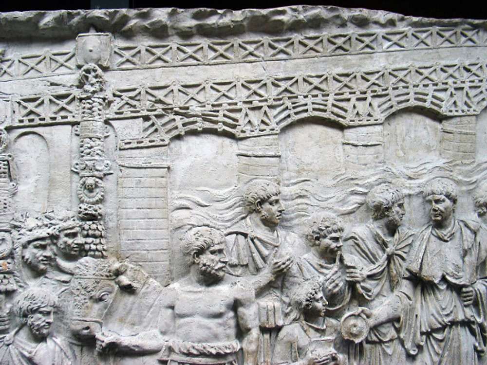 Detail from Trajan's Column showing the bridge across the Danube. Apollodorus is likely one of the men surrounding Trajan.