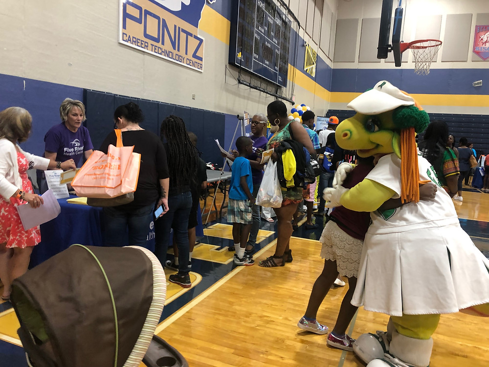 people at vendor tables and a student hugging mascot Gem from the Dayton Dragons