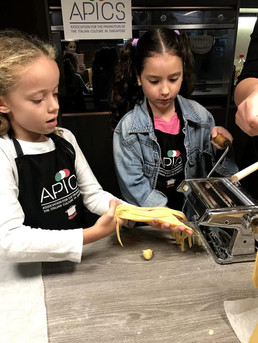 Little chefs rolling fresh pasta