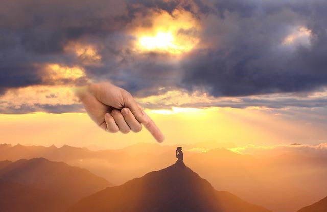 Nainen polvistuu vuorenhuipulla ja valtava syyttävä sormi osoittaa häntä pilvistä