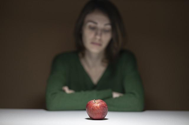 Nainen vihreässä paidassa istuu pöydän ääressä ja tuijottaa punaista omenaa