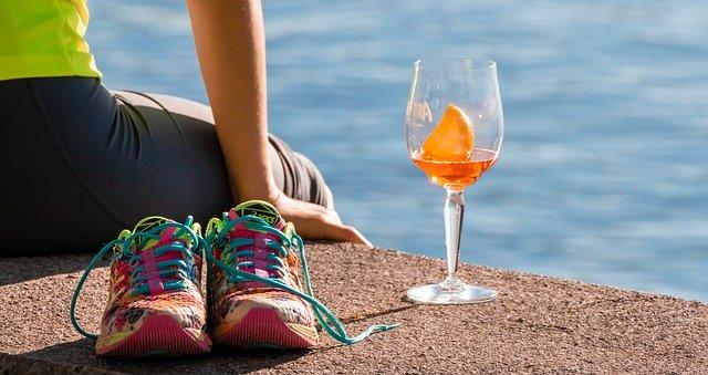 Nainen treenivaatteissa istuu rannalla oranssin juoman kanssa ja lenkkikengät ovat lasin vieressä