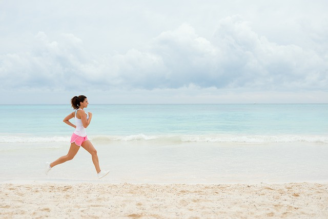 Ruskeahiuksinen nainen juoksee hiekkarannalla pinkeissä shortseissa