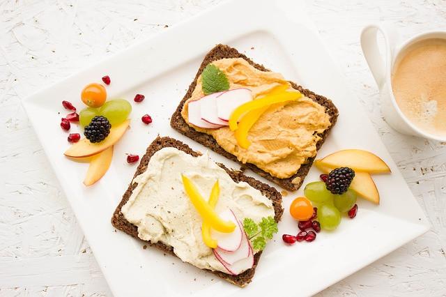 Ruisleipää, hummusta ja hedelmiä kauniisti aseteltuna