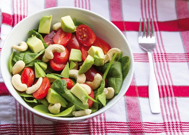 Kuivaa salaattia kulhossa punaruudullisen liinan päällä: pinaattia, cashewpähkinöitä, avokadoa, kirsikkatomaatteja.