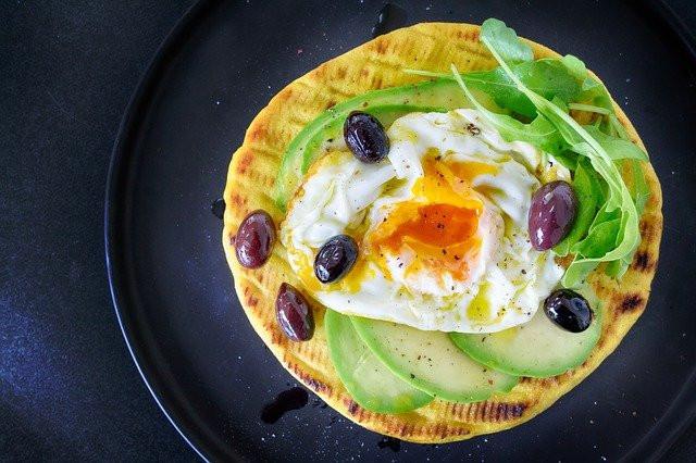 Maissitortilla jonka päällä on avokadoasiivuja, pehmeäksi jätetty paistettu kananmuna, rukolaa sekä tummia viinirypäleitä tummansinisellä lautasella ja pöytäliinalla.