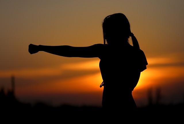 Nainen nyrkkeilee auringonlaskun edessä