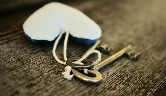 Kaksi avainta ja sydämen muotoinen avaimenperä puisella pöydällä