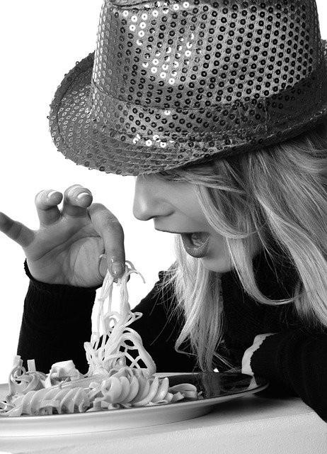 Nainen pitelee spagettia sormillaan