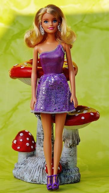 Vaaleahiuksinen barbinukke jolla on lilan värinen mekko ja joka seisoo isojen myrkkysienten edessä.