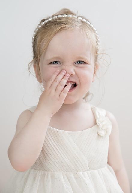 Vaaleahiuksinen tyttö valkoisessa mekossa pitää kättä kasvoillaan
