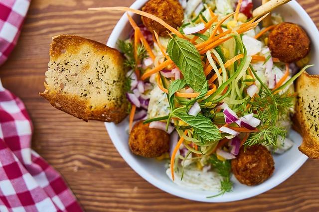 Salaattia, porkkanapyöryköitä, yrttejä ja valkosipulileipää kulhossa