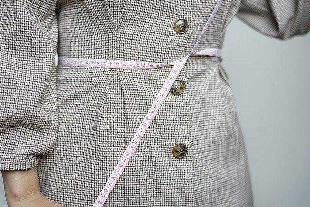 Nainen pitkässä, mustaraidallisessa napitetussa paidassa on sitonut mittanauhan vyötärön ympärille