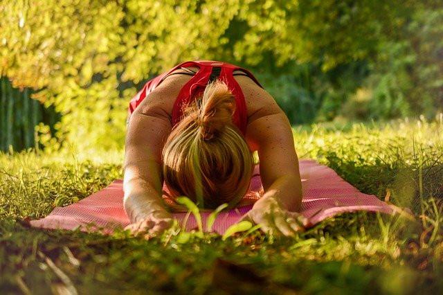 Nainen venyttelee pihalla metsän siimeksessä vaaleanpunaisen joogamaton päällä