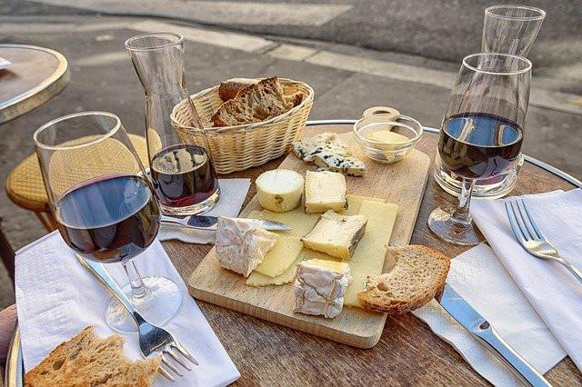 Punaviiniä, leipää ja erilaisia juustoja puisella pöydällä