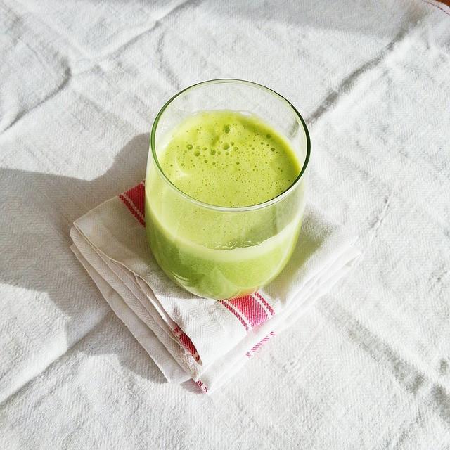 Valkoisella pöytäliinalla vihreää mehua lasissa keittiöpyyhkeen päällä