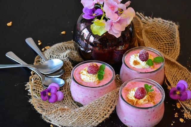 Kukkia, luskoita ja pinkki jälkiruoka vadelmista