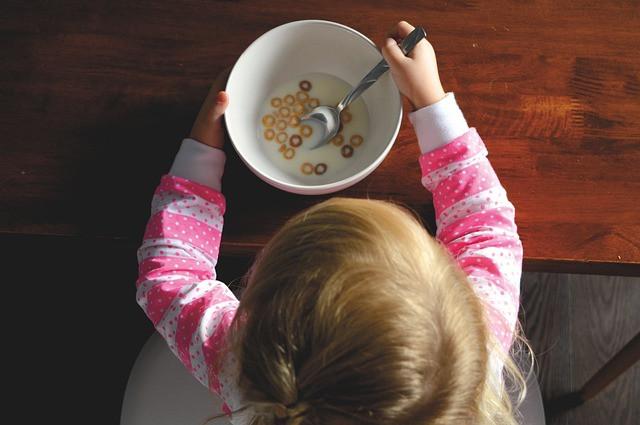 Pieni tyttö istuu pöydän edessä ja syö muroja