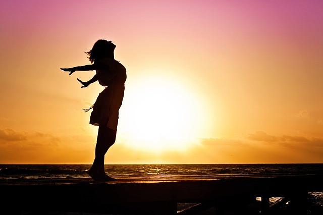 Elämästään nauttiva nainen auringonlasku taustalla