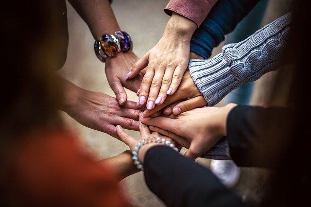 Ihmisten käsiä päällekkäin