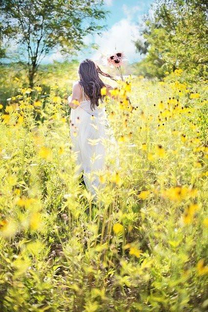 Ruskeahiuksinen nainen pitkässä valkoisessa mekossa aurinkoisella niityllä, jossa on keltaisia kasveja