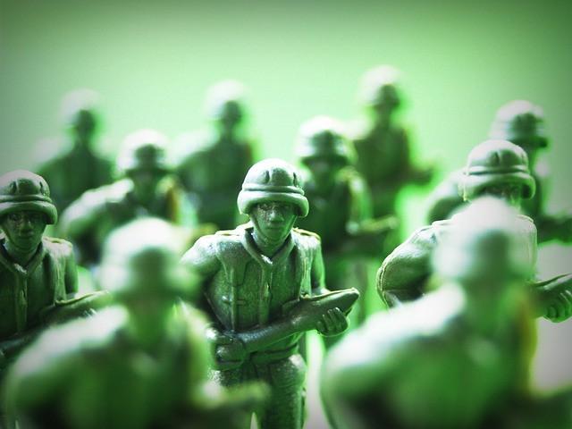 Vihreä tausta ja vihreitä lelusotilaita hyökkäämässä