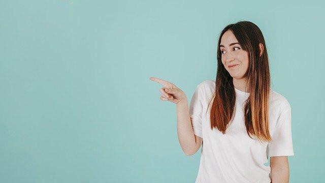 Ruskeahiuksinen nainen osoittaa sormella sinivihreällä taustalla