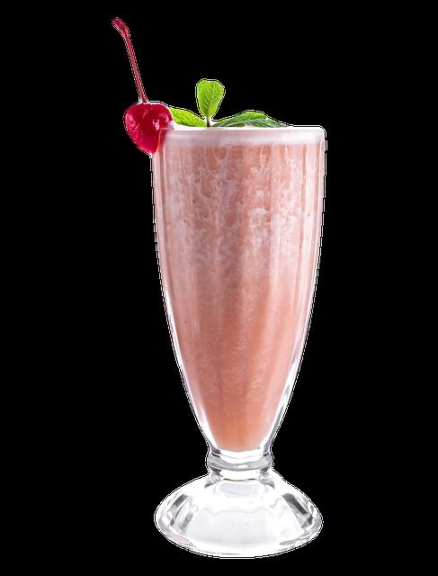 Vaaleanpunainen pirtelö lasissa kirsikan ja mintunlehtien kera