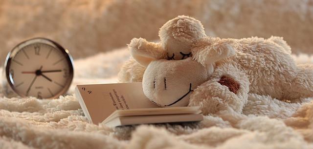 Valkoinen pehmolelu-lammas on nukahtanut kirjan ääreen ja taustalla on herätyskello