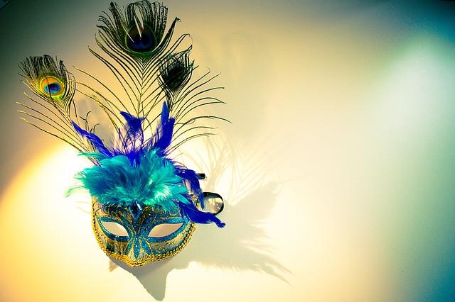 Venetsialainen kullan ja turkoosin värinen kimaltava naamio, jossa on turkoosin ja lilan värisiä höyheniä sekä riikinkukon sulkia
