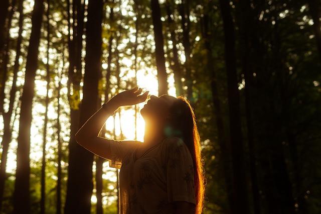Nainen seisoo metsässä auringonlaskun aikaan